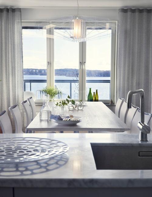 Från köket har man utsikt över fjärden. Matbordet har Gun låtit tillverka. Transparenta gardiner, Kinnasand. Tallrikar, Gustavsberg. Flaskor och små glasvaser med murgröna, Asplund.