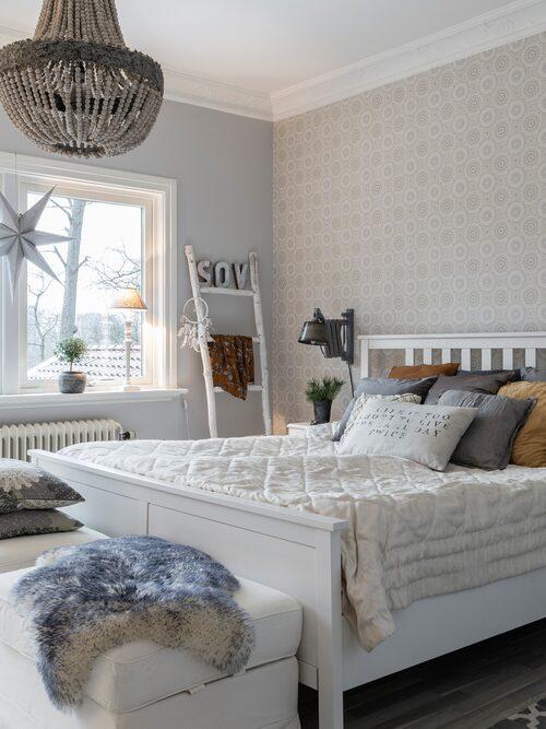 Sofia och Mikaels sovrum ligger på andra våning. Här går julen i lite ljusare toner med julstjärnor i vitt och gedigna fårskinn som ger en ombonad känsla. Lampa, Olsson & Jensen. Säng, Ikea. Kuddar från Mio, Rusta och Åhléns.