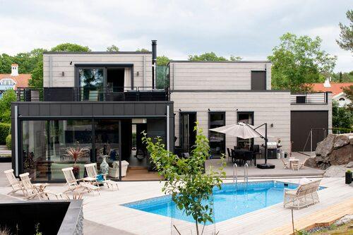 På baksidan av huset öppnar de stora fönsterpartierna upp mot poolområdet och trädgården. Här är det aktivitet så fort vädret tillåter och poolen används flitigt av hela familjen.