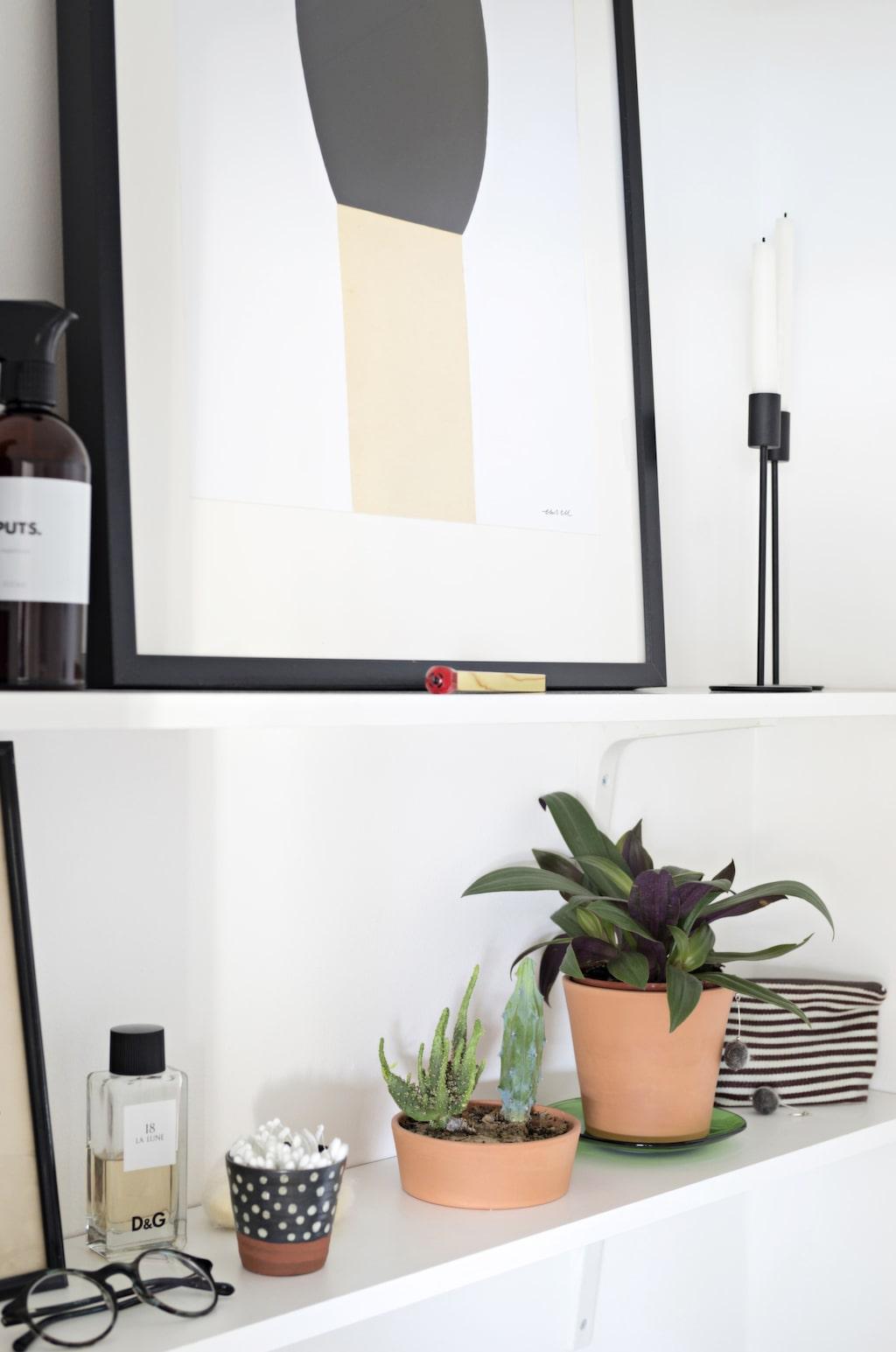 På enkla, vita konsolhyllor samsas praktiska och vackra saker.