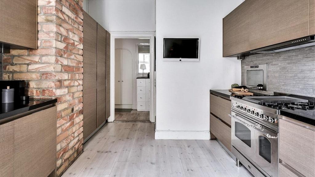 Vita väggar och framtaget tegel, även här ligger brädgolv. I anslutning till köket finns en separat matsal med inbyggd vinkyl. Plats för stort matsalsmöblemang.