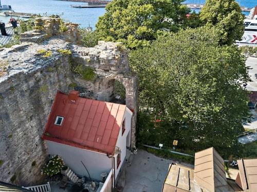 Två av husets väggar sitter ihop med ruinen av Visborgs slott.