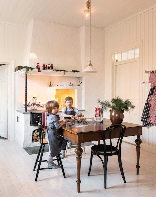 Båda pojkarna gillar att baka och hjälpa till med matlagning. Barnförkläden, Hemtex. Öglanstolen är en av fyra som stod på vinden när familjen köpte huset. Skomakarlampa, Karlskrona lampfabrik. Tomtar på spiselkransen, Hemtex. Kökshanddukar, Nyblom Kollén.