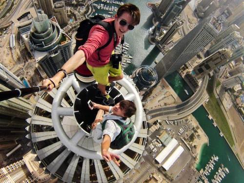 Ryssen Alexander Remnev, i röd skjoirta, är en som tar våghalsiga selfies. Här klättrar han tillsammans med en kompis upp på toppen av Princess Tower i Dubai.