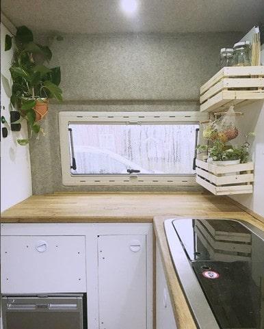 Köksdelen är utrustad med både skåp, hyllor, spis och diskho.
