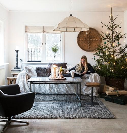 Vardagsrummet är inrett med en mix av saker, och möbler i från olika tidsepoker. Julgranen står i en gammal korg, och är sparsamt dekorerad med gamla julgranskulor i grönt. Ljusstaken och julgransbelysningen med höga ljus kommer från Konstsmide.
