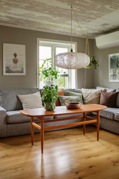 I vardagsrummet har taket patina och ett teakbord vid soffan. Soffa, Ikea. Lampa, Lampverket. Tryck på väggen, Fotografiska.