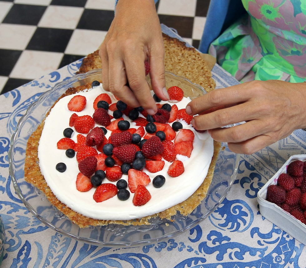 Martina ställer fram en ljuvlig knäckflarnsbärstårtan, som hon gjort på knäckflarnsbotten, vispgrädde och jordgubbar, blåbär och hallon.