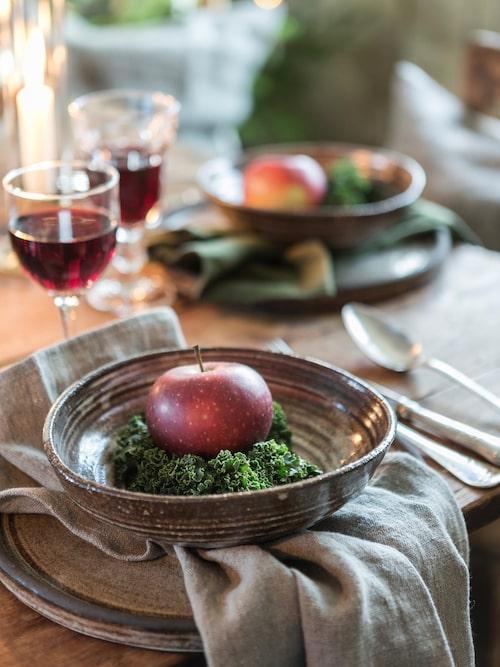 Duka dekorativt med rustikt porslin och toppa med äpplen och grönkål så är julkänslan i hamn. Oval skål i lera, Taste, diameter, 20 cm, 249 kr och mattallrik, Taste, diameter, 26 cm, 349 kr, Västergården. Rustik linneservett Natural beige, 99 kr, Lovely Linen. Udda vinglas är inköpta på loppis.