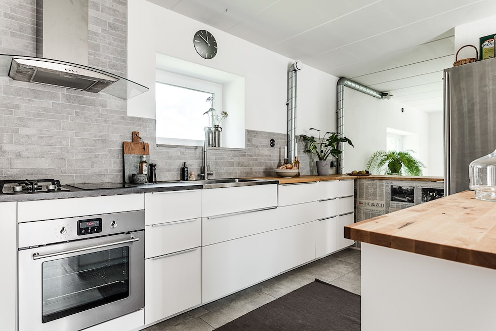 Köket som uppdaterades i år är komplett med kyl/frys, spis, ugn, diskmaskin och fläkt. Klinkers på golv, vita luckor och generös arbetsyta.
