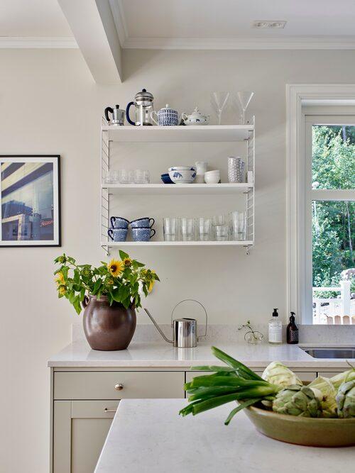 På en hylla i köket står glas och koppar lättillgängligt. Grönt fat, Fårö Krukmakeri. Bänkskiva i komposit, Silestone. Hylla, String. Höganäskruka, loppis. Vattenkanna, Stelton.