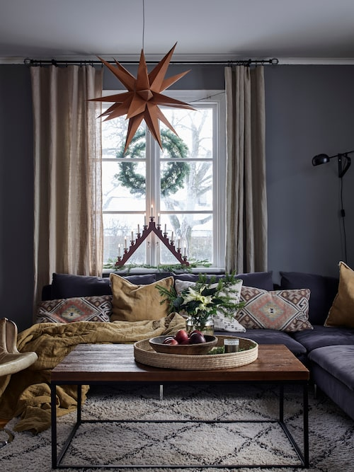 Brända saffranstoner på kuddar och plädar i soffan ger rummet en varm ombonad känsla.
