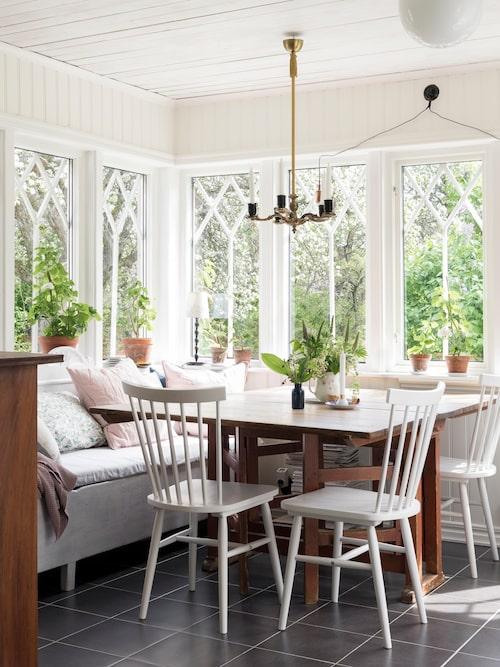 På glasverandan står en kökssoffa som Lindas gammelfarmor och gammelfarfar fick i bröllopspresent. De nya fönstren i gammal stil släpper in mycket ljus i huset.