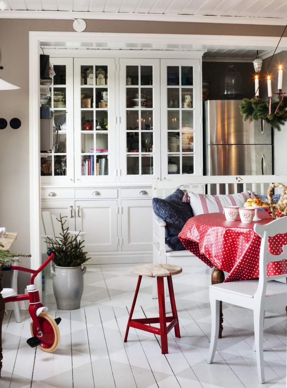 Köket är platsbyggt från Fisketorps snickeri. Soffa, bord, stolar och julkudde kommer från Utängs antik. Den grå fårskinnskudden är från Shepherd, julporslin från Greengate och den rödlackerade pallen kommer från House doctor.