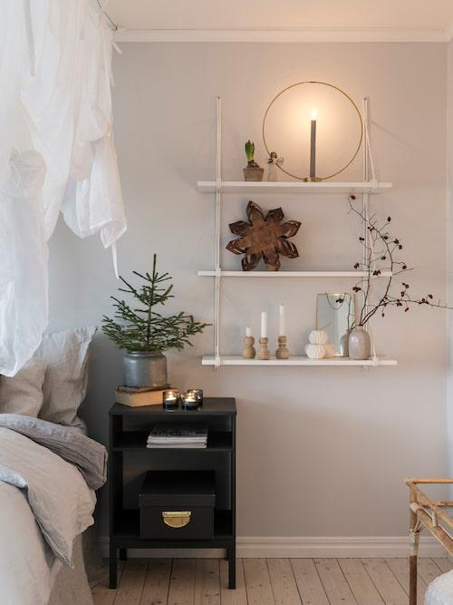 Ida och Kristofer brukar pynta överallt med granar, enar och tallar i olika storlekar. Det är ett enkelt sätt att skapa stämning inomhus. Hylla, Ikea.