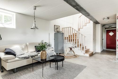 Polerade betonggolv, putsade vita väggar och djupa fönsternischer präglar hemmet.