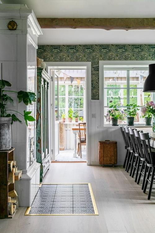 Den gamla kakelugnen tänds under hela året, både för värme och gemyt. Verandan är ett öppet uterum som släpper in ljuset i köket. Tapet, William Morris.