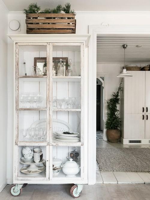 Ovanpå vintrinskåpet står en gammal träback som Sandra lagt tallris i. Enkelt, och ger fin julstämning. Sandra har ritat skåpet och Mikael har tillverkat det efter hennes önskemål, som dörr användes gamla fönster med munblåst glas. I rummet innanför huserar kyl och frys som ryms bakom de råspontsbeklädda dörrarna med läderhandtag.