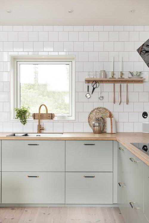Köket är ljusgrönt med ljust trägolv och kaklade vita väggar.