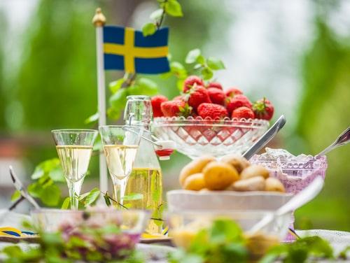 En typisk midsommarbuffé brukar innehålla sill och potatis, kanske en nubbe och en hel del jordgubbar.