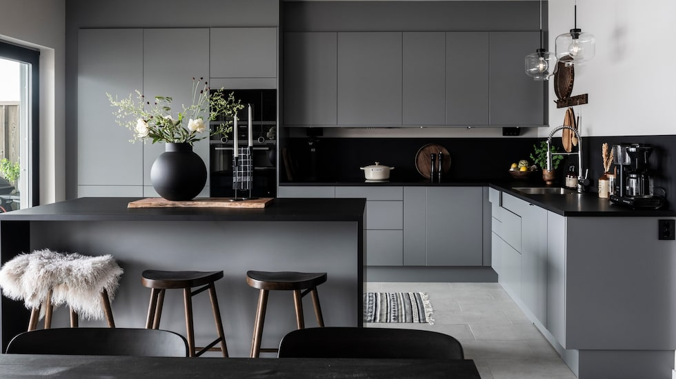 Bänkskivan i svart laminat fortsätter upp på väggen som stänkskydd och förstärker kökets karaktär. Mellangrå kök, Arkitekt Plus, Marbodal. Barstolar, Ellos.