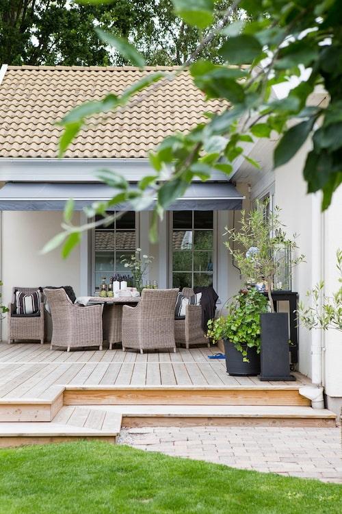 Närmast huset är trädäcket möblerat med en matgrupp i konstrotting som tål att stå ute året om. Om solen är för stark finns markiser att fälla ut, så att man kan sitta i skugga även här.