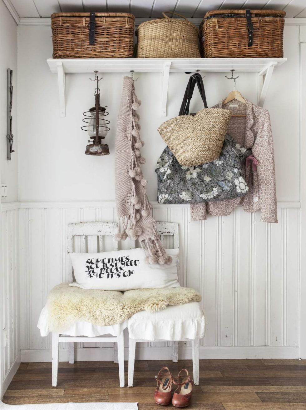 Låt din inredningsstil gälla även i hallen. Här lantligt romantiskt med rustika korgar, väggpanel, gamla stolar och fårskinn.