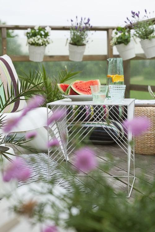 Svalkande melon och smaksatt vatten serveras på balkongen. Bord, Lagerhaus.