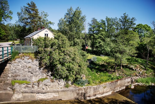 Från en bro ser man hur huset ligger fint vid ån, med en sluttande tomt och en mysig syrenberså.
