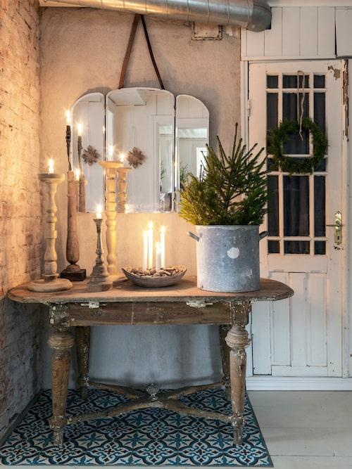 Årets adventsljusstake är arrangerad i ett gammalt träfat, omgärdat av nötter. Innanför den gamla dörren med krans av lingonris hängande på finns skafferiet.