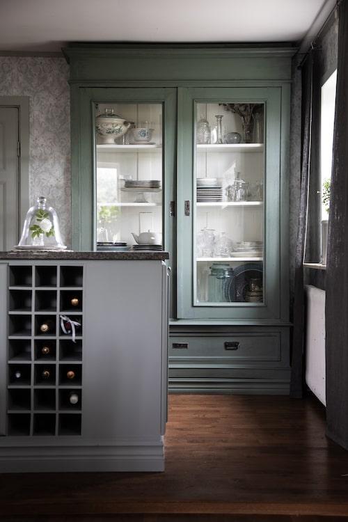 Det vackra skåpet köpte Åsa på auktion. Det fick byggas om lite, för att passa in. När köket renoverades fick skåpet en grågrön färg med koden 2005G20Y. Köksön är byggd av en del av köksskåpen, som togs bort vid den första köksrenoveringen.