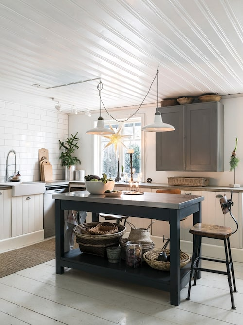 Familjens kök är hemtrevligt och gediget med golv som har många år på nacken – paret köpte det begagnat, då det tidigare har legat som golv i ett gammalt hus. Köket är byggt av gamla möbler, som vedlår och antika köksskåp, blandat med underskåp från Ikea som har fått hemmagjorda luckor av kvistfri furu. Den praktiska köksön med plåtbeklädd bänkskiva är tillverkad av en väns morfar. Vask från Ikea och blandare från Grohe. I fönstret hänger en pappersstjärna från Konstsmide.