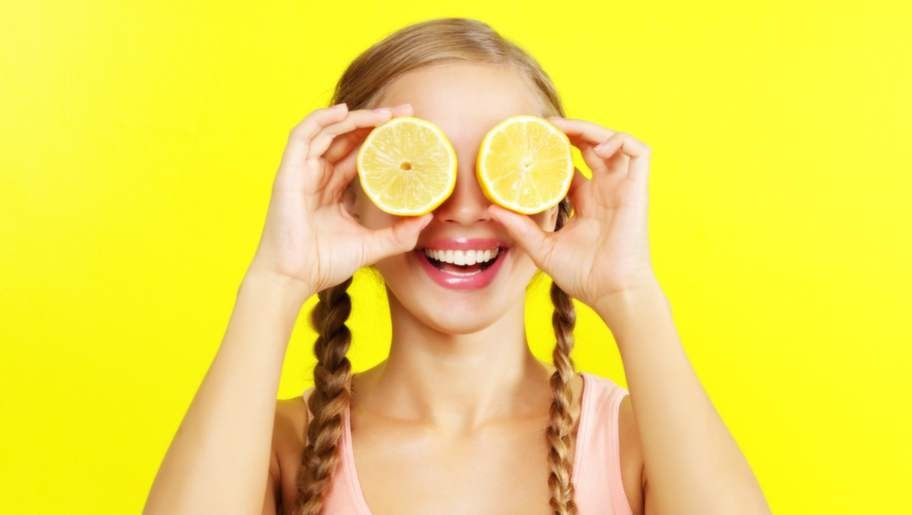 young girl holding lemons on yellow background