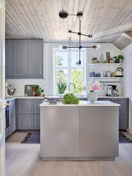 Det vitlaserade trätaket ger köket en ombonad känsla. Paret är glada att de satte in en köksö i köket. Bänkskivan på köksön är en kompositskiva i marmor, Stenskivor.se. Kök, Ikea. Lampa, House Doctor. Pionerna har Therése plockat in från den prunkande trädgården. Vas, Hemtex. Skål, arvegods.