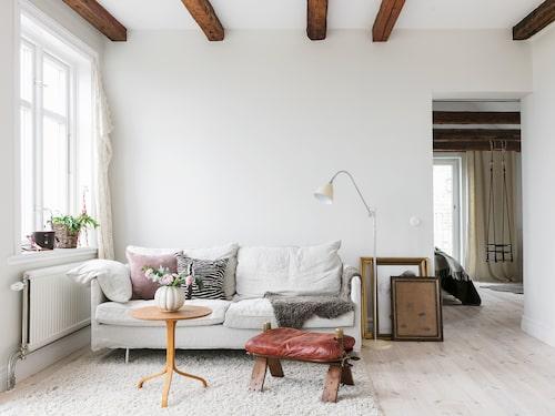 """Allrummet på ovanvåningen har ingen tv och är ett riktigt """"umgängesrum"""". Pallen som är en kamelsadel är köpt på loppis. Den ljusa sofffan kommer från Sits och golvlampan från Gubi."""