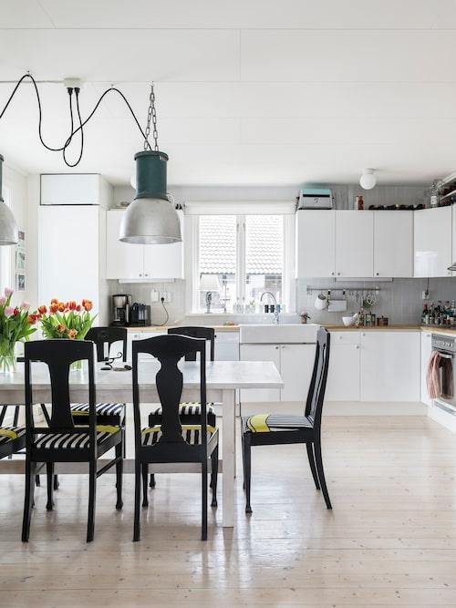"""Köket går i vitt och får karaktär av Hanna och Björns superfynd, """"gresalamporna"""", Siemens från 1950-talet. Vita köksskåp och matbord, Ikea. De omklädda stolarna är en blandad kompott. En del av stolarna, Äpplet från 1900-talets början, kommer från Hannas mormors barndomshem, resterande stolar är tillverkade av Björns farfars bröder."""