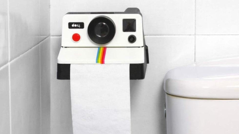 En polaroidkamera på toan spottar ur sig toapapper i stället för bilder.