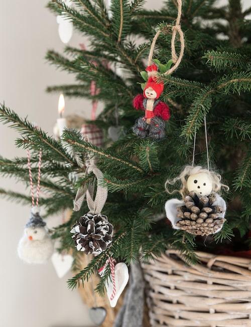 På skänken står en liten gran som är dekorerad med julgranspynt, mestadels gjort av barnen.