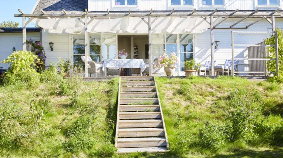 Branten är trädgårdens vilda blomsteräng och den praktiska trappan leder ner till gräsmattan och resten av trädgården.