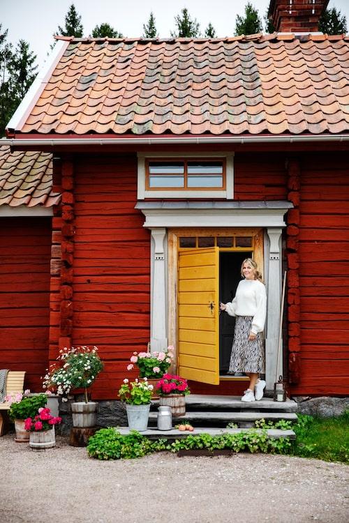 Emma-Lisa på trappen till sitt renoverade hus. Dörren i ockragult kommer från Dalfors snickeri.