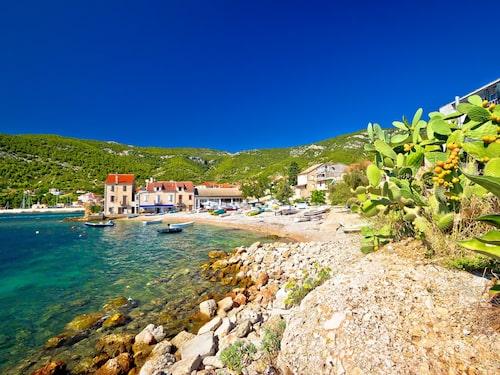 Härlig natur, vackra stenhus och turkost vatten i rofyllda fiskebyn Komiza i Kroatien.