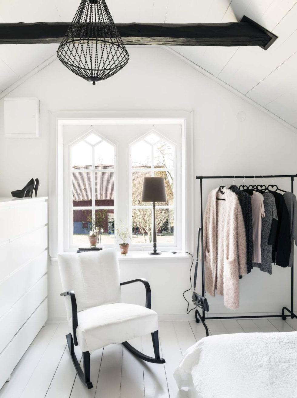 Parets sovrum har tak upp till nock med synliga bjälkar som har vaxats mörka för att skapa kontrast till den vita inredningen.