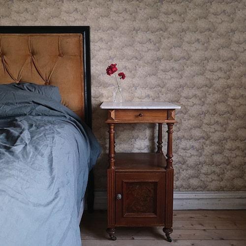 I sovrummet på övervåningen fanns fina trägolv, pappspänt tak, en liten gjutjärnskamin som blev som ny efter att de putsat upp den med spissvärta. Här fanns och den första tapeten bevarad, som förmodligen tillkom runt 1910.