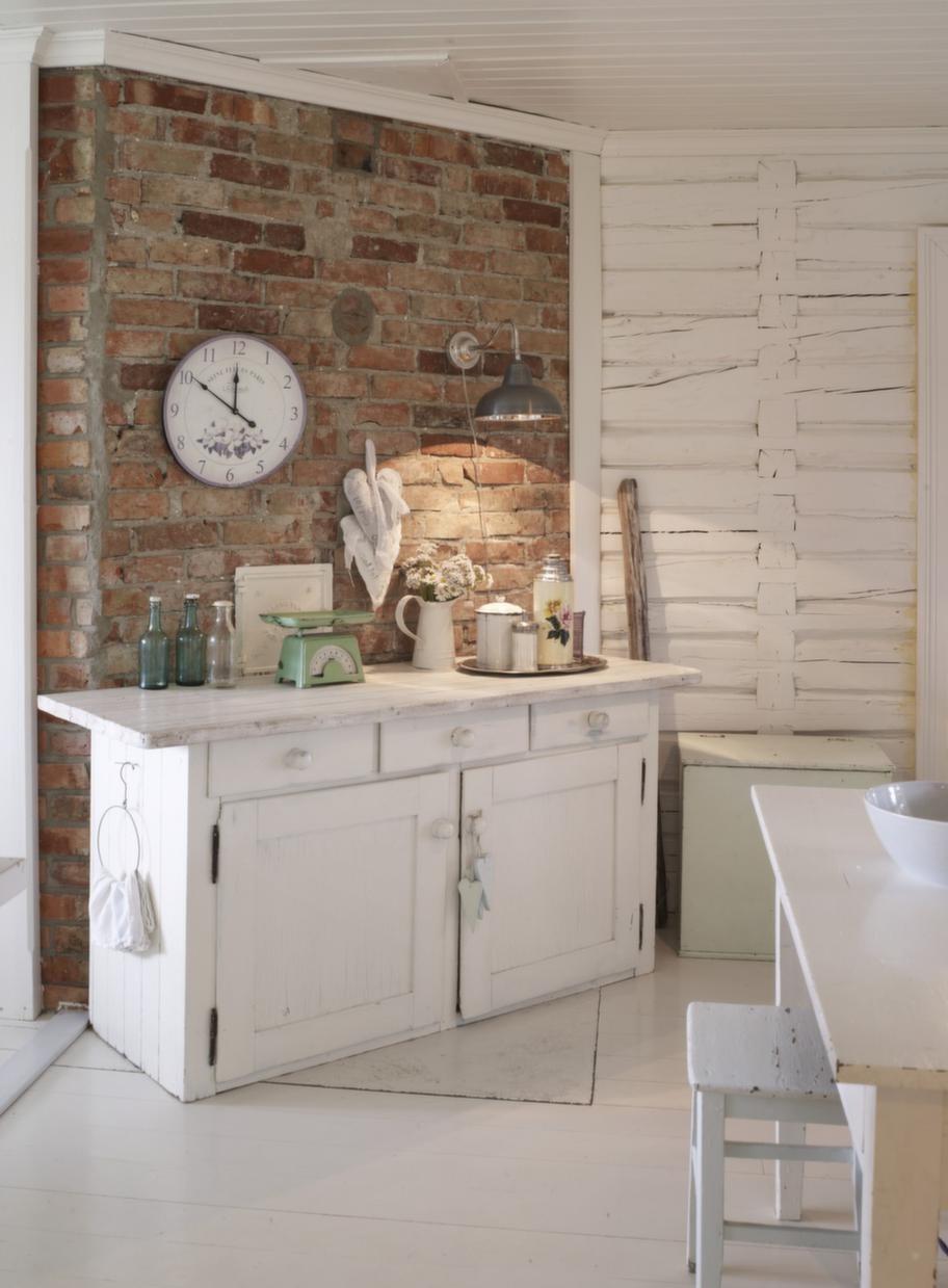 Kontraster. Murväggen blir en effektfull kontrast till de vita golven och väggarna i köket. Det lite ruffiga uttrycket förstärks ytterligare av industrilampan på väggen.