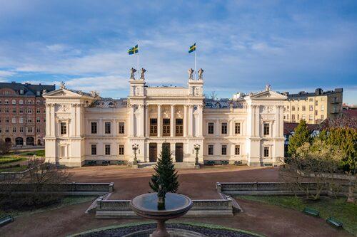 """Högst upp på Universitetshuset, invigt 1882, stavar gyllene bokstäver """"Regia Academia Carolina"""", Kungliga Karolinska akademien, universitetets ursprungliga namn."""