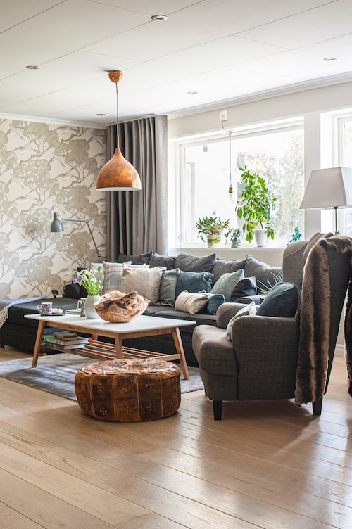 I vardagsrummet sitter en tapet som passar fint ihop med övriga färger och skapar ett lugn i rummet trots sitt mönster. I soffan kuddar av diverse tyger från Romo, Ralph Lauren och Villa Nova, uppsydda av Inredningskreatören. Golv i ek, Tarkett. Tapet, Mulberry. Fåtölj, Ikea. Fotpall i skinn, loppisfynd.