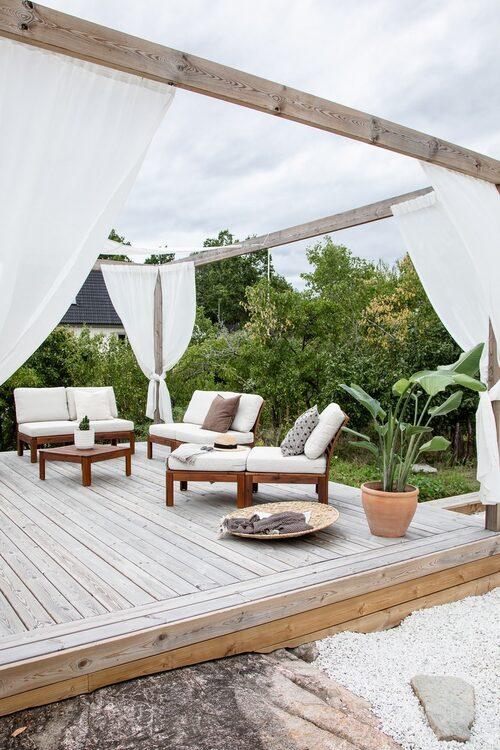 Loungegruppen kan enkelt flyttas och byggas om till en stor soffgrupp eller till en solsäng beroende på tillfälle. Både seglarduken och gardinerna är lätta att ta fram eller ta bort beroende på om man vill ha sol eller skugga. Loungemöbler, Ikea.