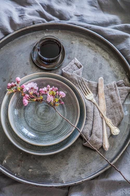 En japansk körsbärskvist passar fint i en stilren och lite rå dukning där den poppar extra mycket mot de grövre materialen.