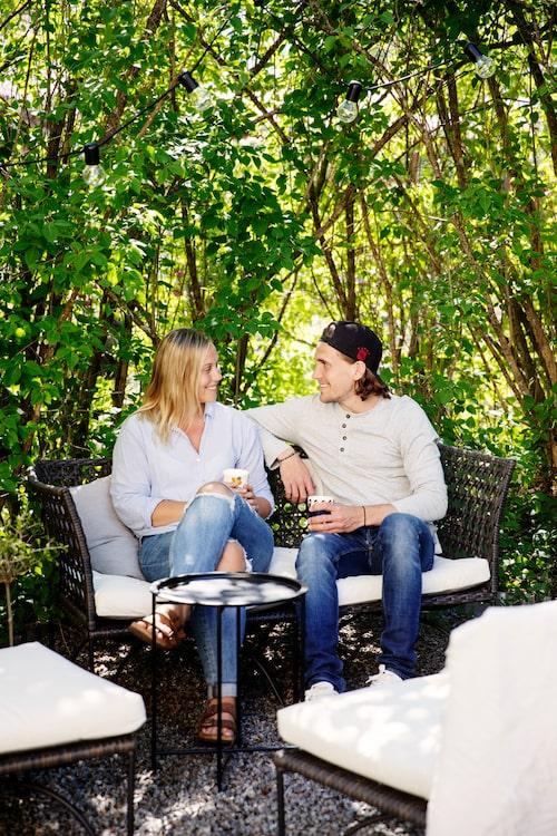 Evelina och Robin i soffa som finns bredvid grillplatsen. Soffa, bord och stolar, Ikea.