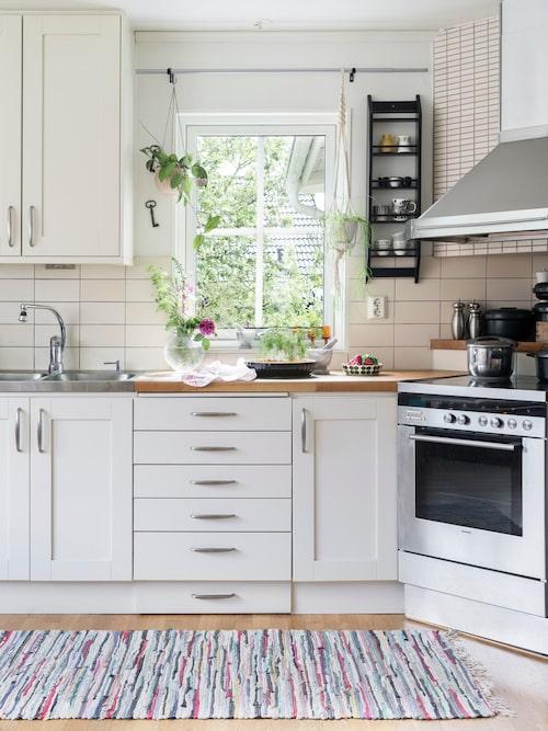 Köket har fått en lantlig touch med vitt kök och trasmatta. Kök, Vedum.